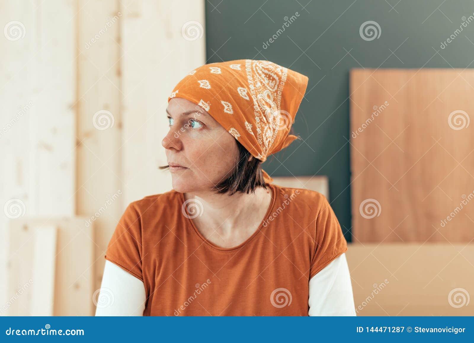 Zelf - tewerkgestelde vrouwelijke timmerman die uit het venster kijken