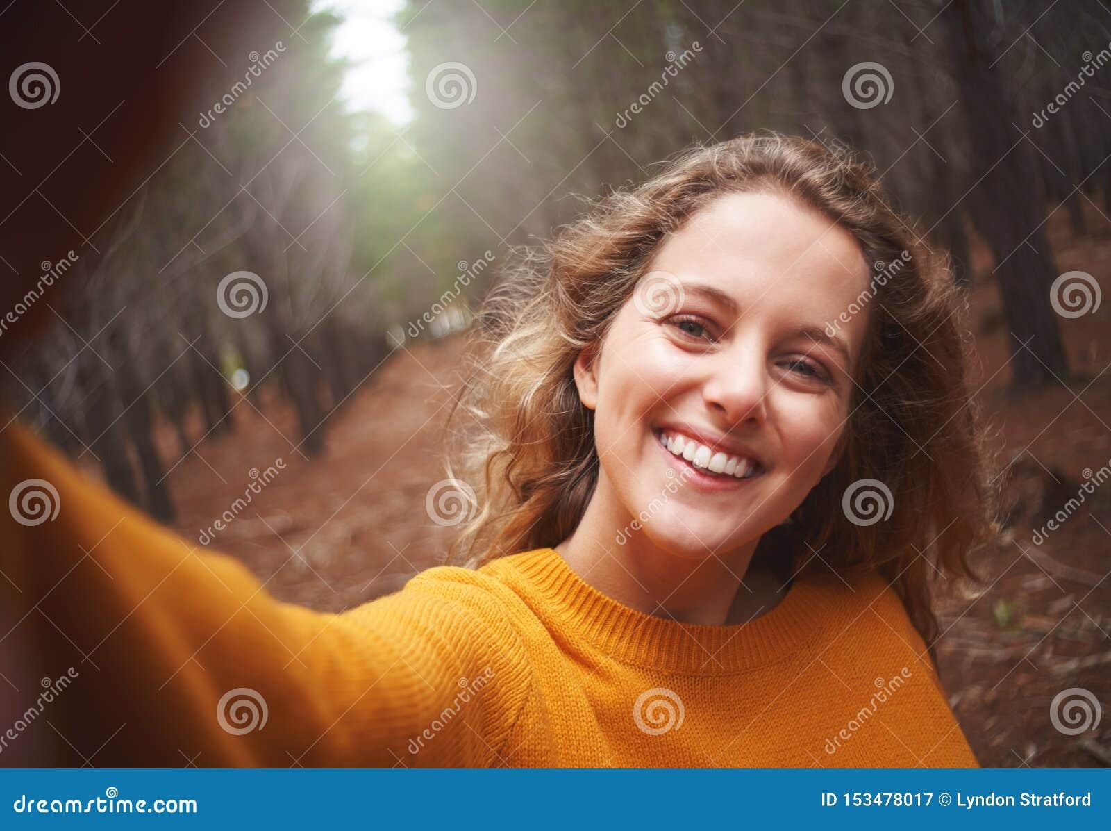 Zelfportret van speelse glimlachende jonge vrouw
