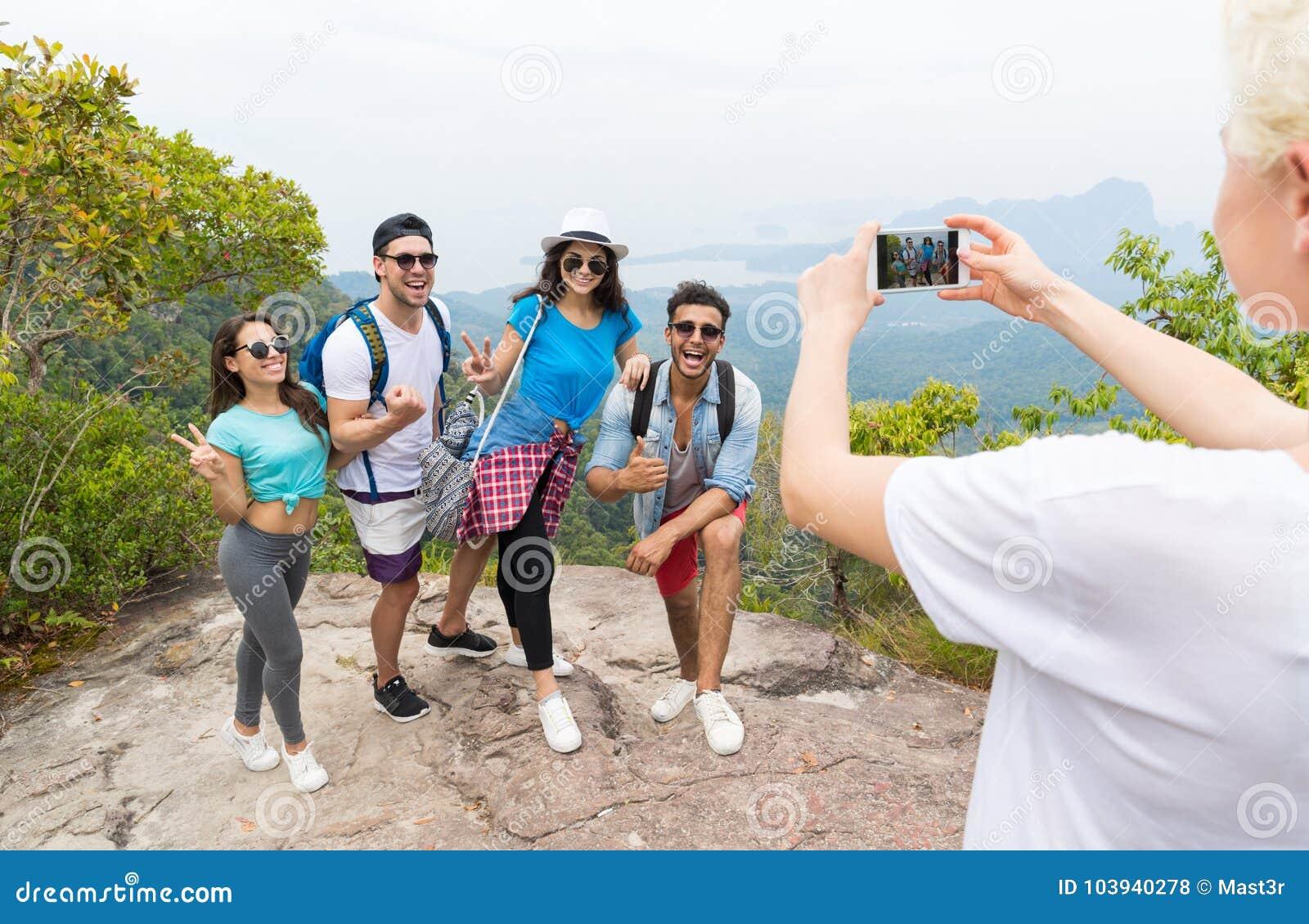 Zellintelligentes Telefon, das Foto der netten touristischen Gruppe mit Rucksack über Landschaft von der Gebirgsspitze, Leute-Auf