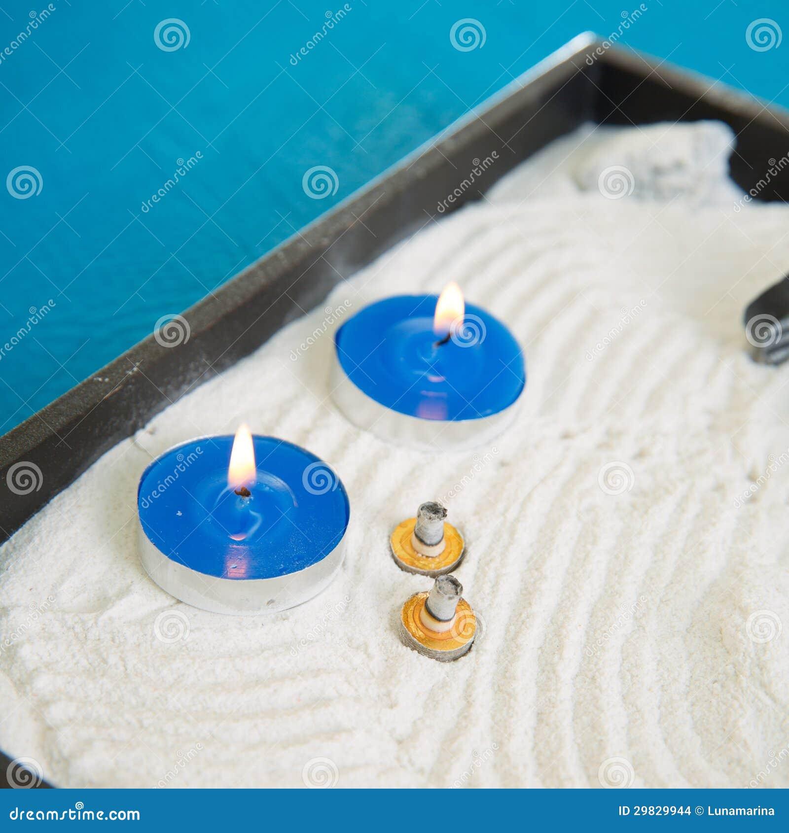 Zen pouco jardim com velas e o moxa azuis