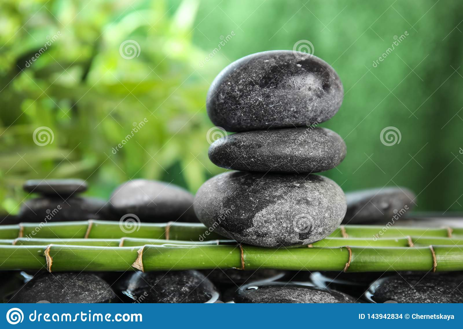 Zen stones on bamboo against background