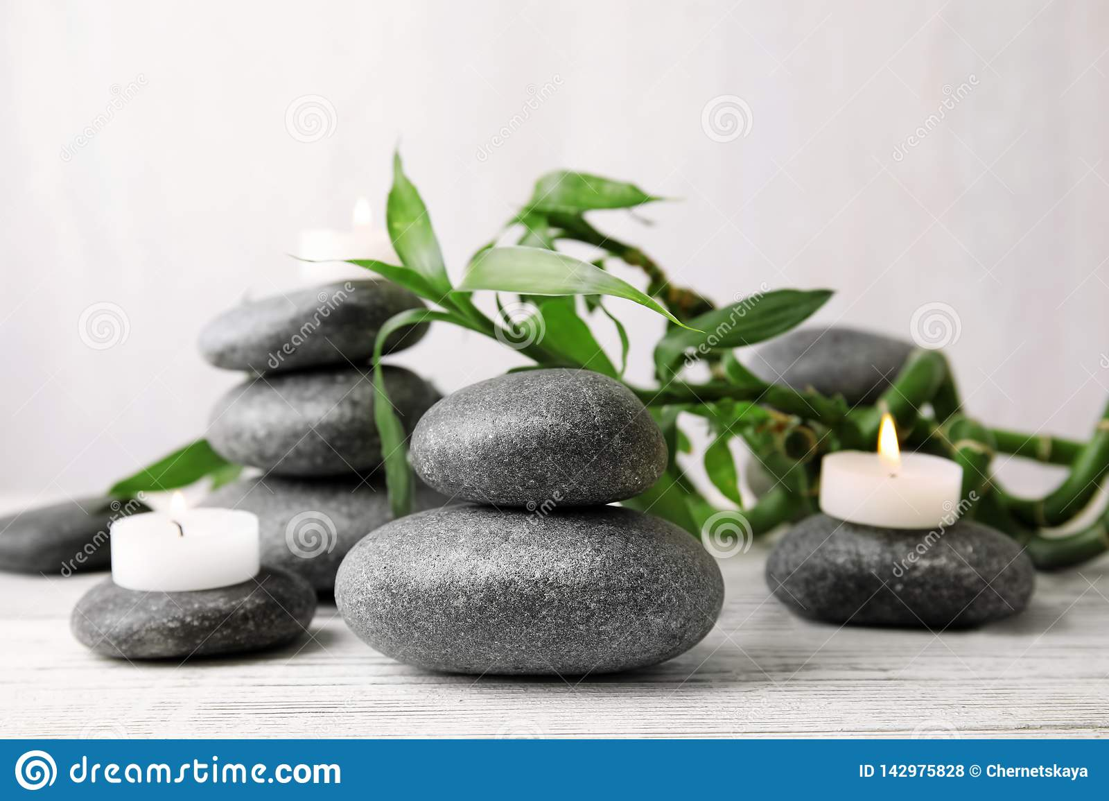 Zen stones, bamboo and lighted candles on table