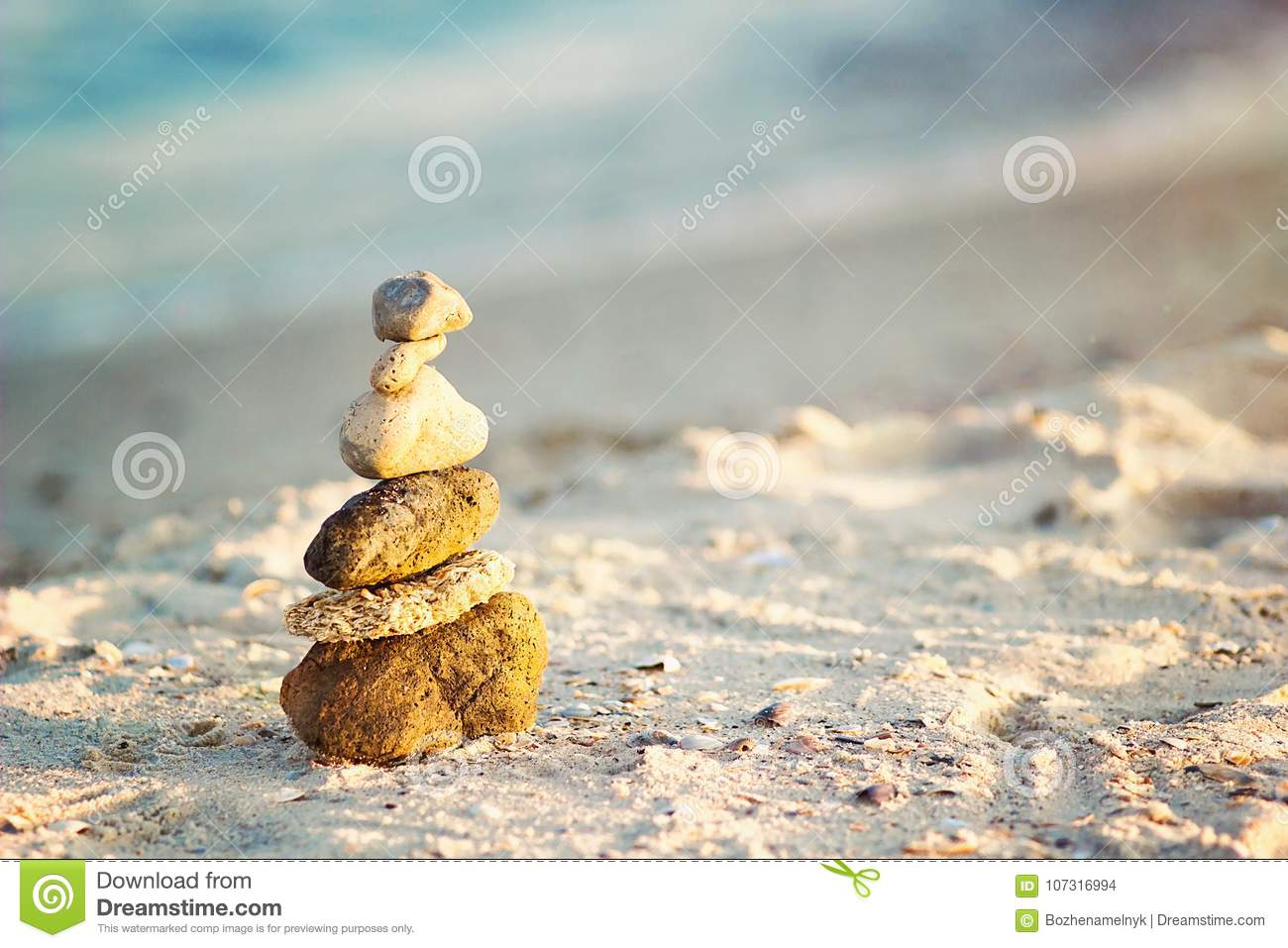 Zen Stones on beach for perfect meditation. Calm zen meditate background with rock pyramid on sand beach symbolizing stability, ha