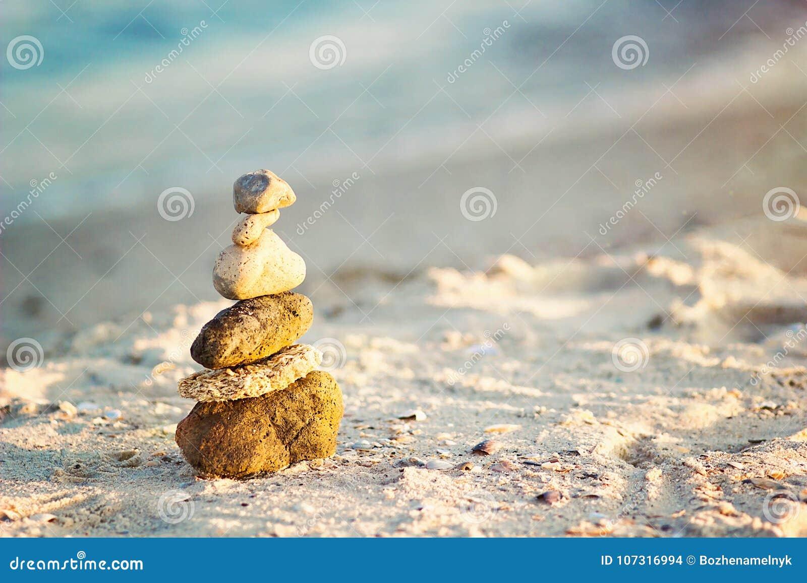 Zen Stones på stranden för perfekt meditation Den lugna zenen mediterar bakgrund med vaggar pyramiden på sandstranden som symboli