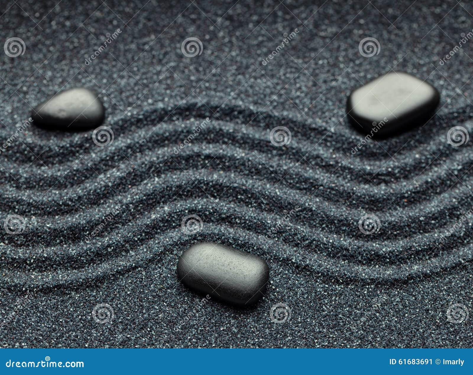 Zengarten mit einer Welle zeichnet im Sand mit entspannenden Massagefelsen