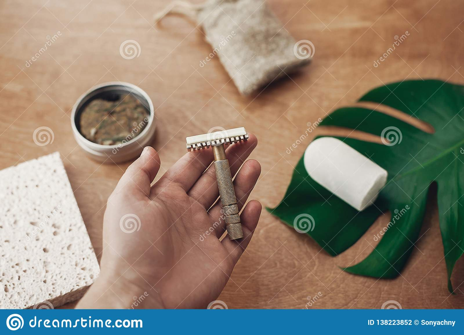 Zero waste, plastic free beauty essentials. Hand holding reusable razor for shaving on background of natural soap, solid shampoo,