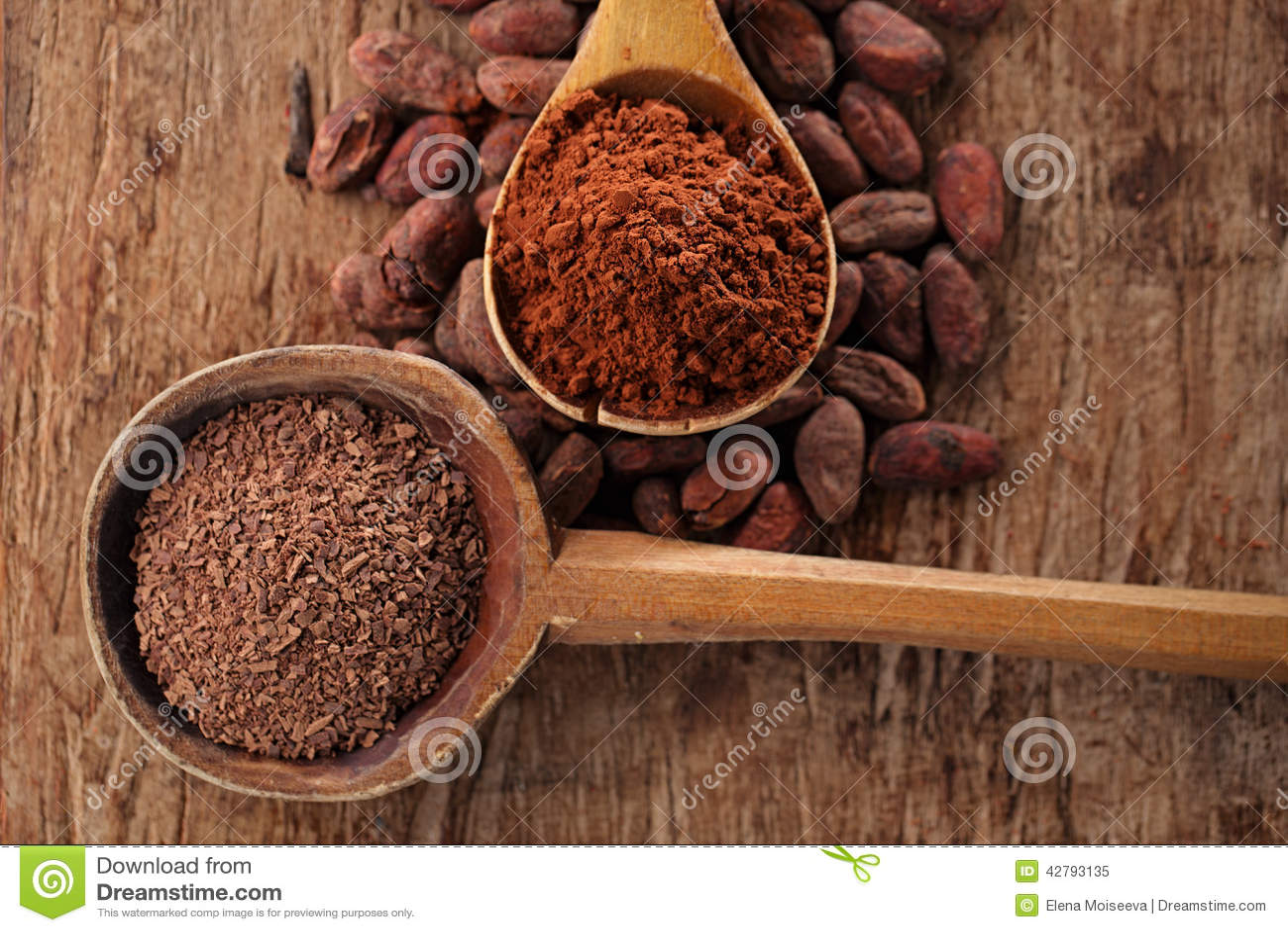 Zerriebene dunkle Schokolade im alten hölzernen Löffel auf gebratenem Kakao choco