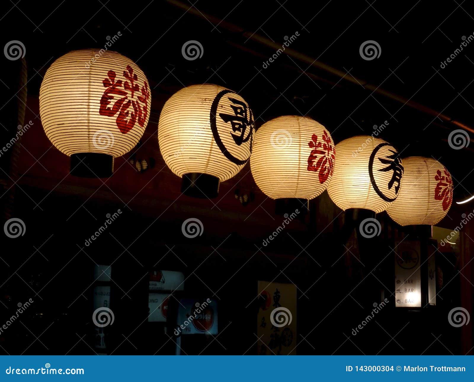 Zes traditionele Japanse document lantaarns die buiten een restaurant in Kyoto hangen