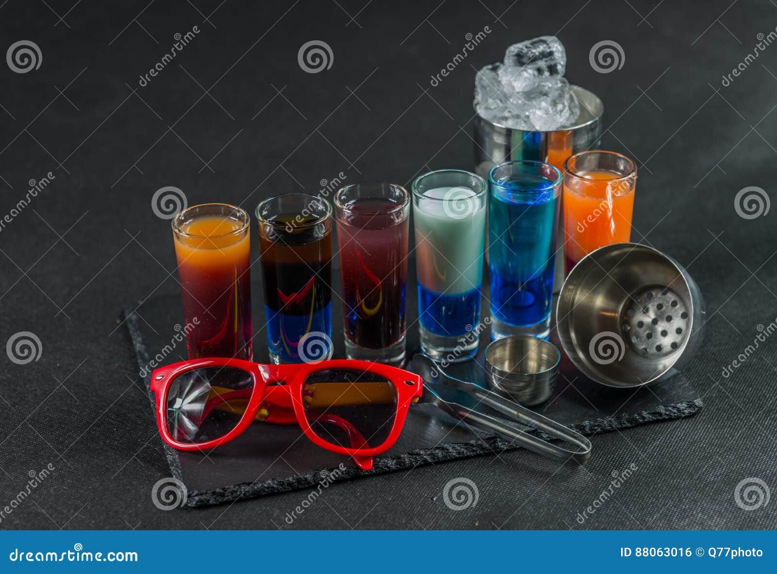 Zes verschillende gekleurde geschotene die dranken, op een zwarte steenpla worden opgesteld