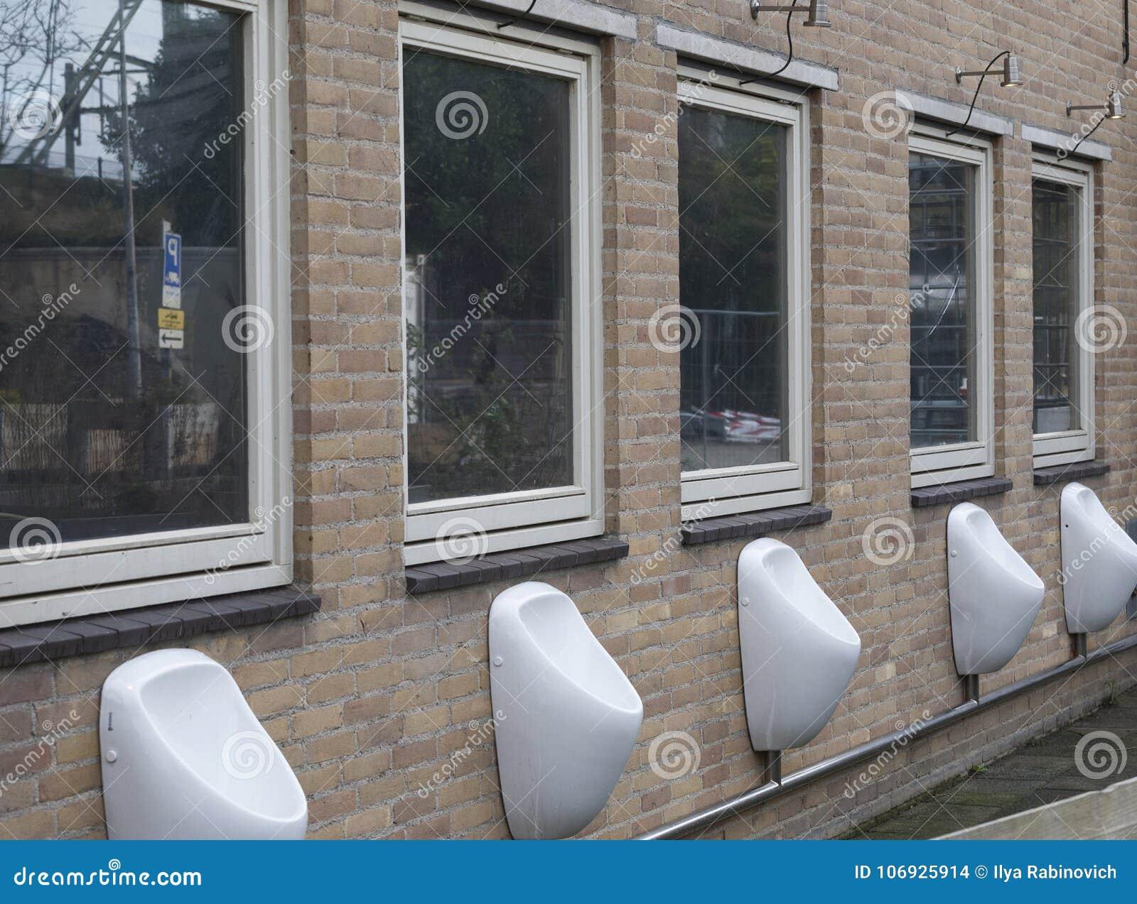 Zetten Mensen` s openbare pissoirs op een muur in centrum van Amsterdam op,