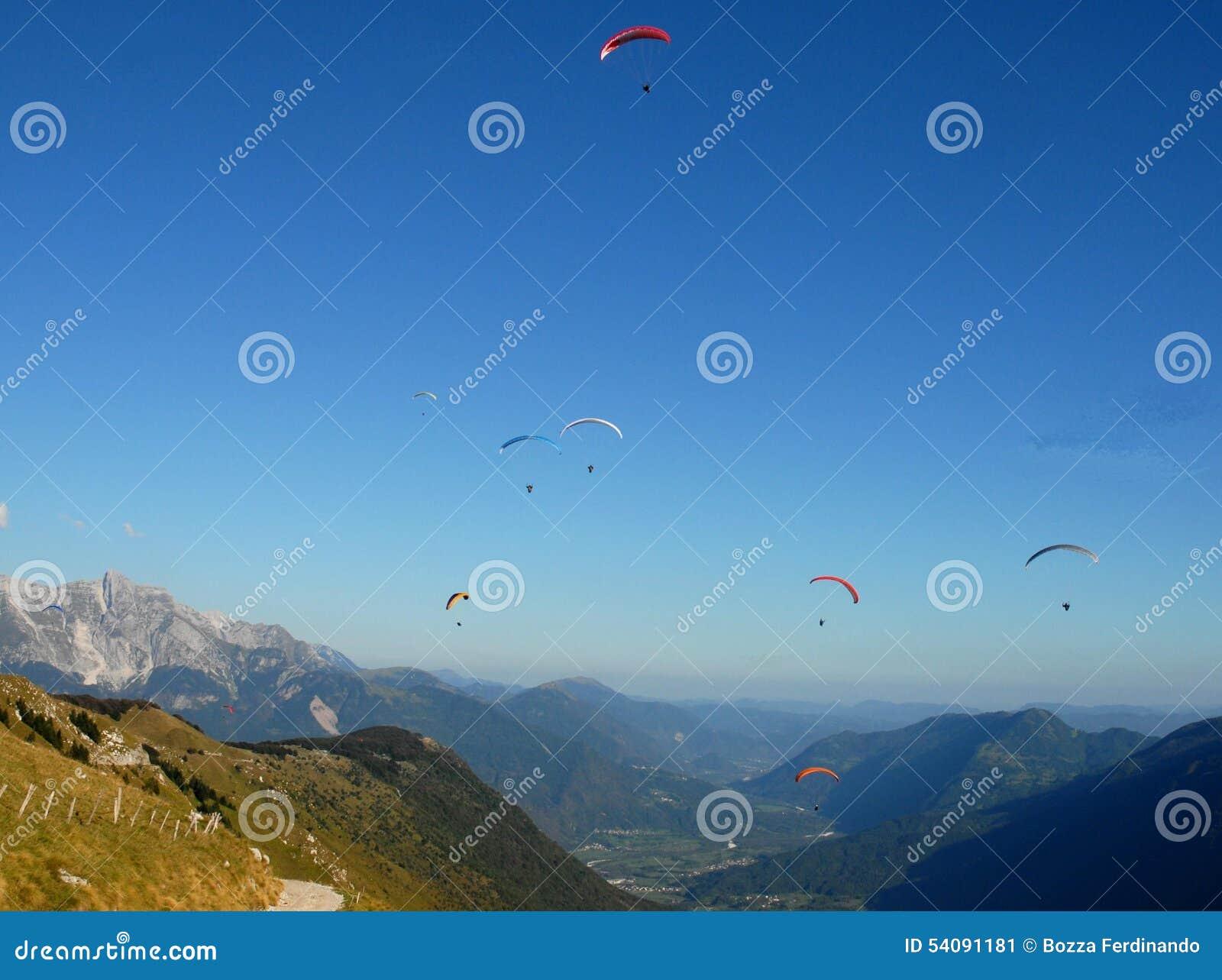 Zeven kleurrijke hangen-zweefvliegtuigen in de blauwe hemel