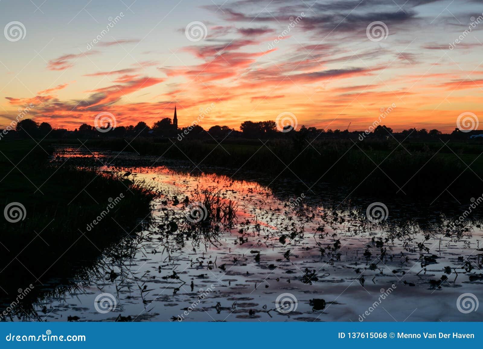 Zgłębia - czerwonego i pomarańczowego niebo z odbiciami w wodzie kanałowy pobliski Gouda holandie