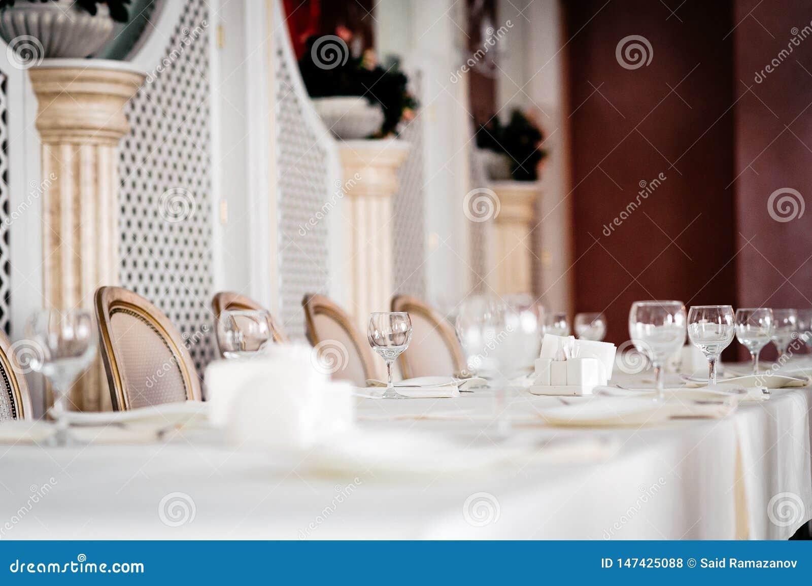 Zg?asza set dla bridal przyj?cia, bia?ego tablecloth i bielu z z?ocistymi krzes?ami,