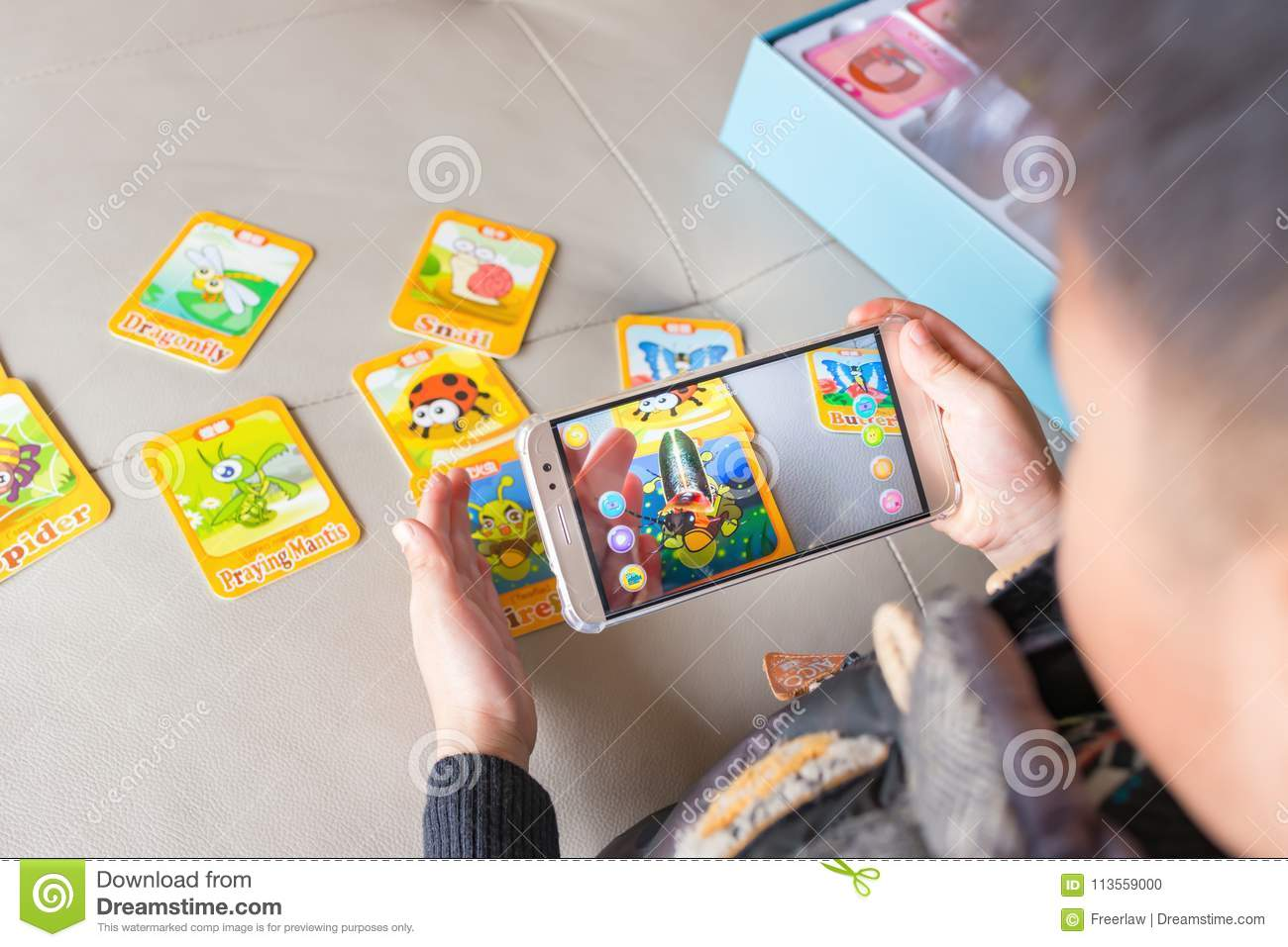 Zhongshan,China-December 30, 2017:kid playing Augmented Reality popup of ladybird via mobile