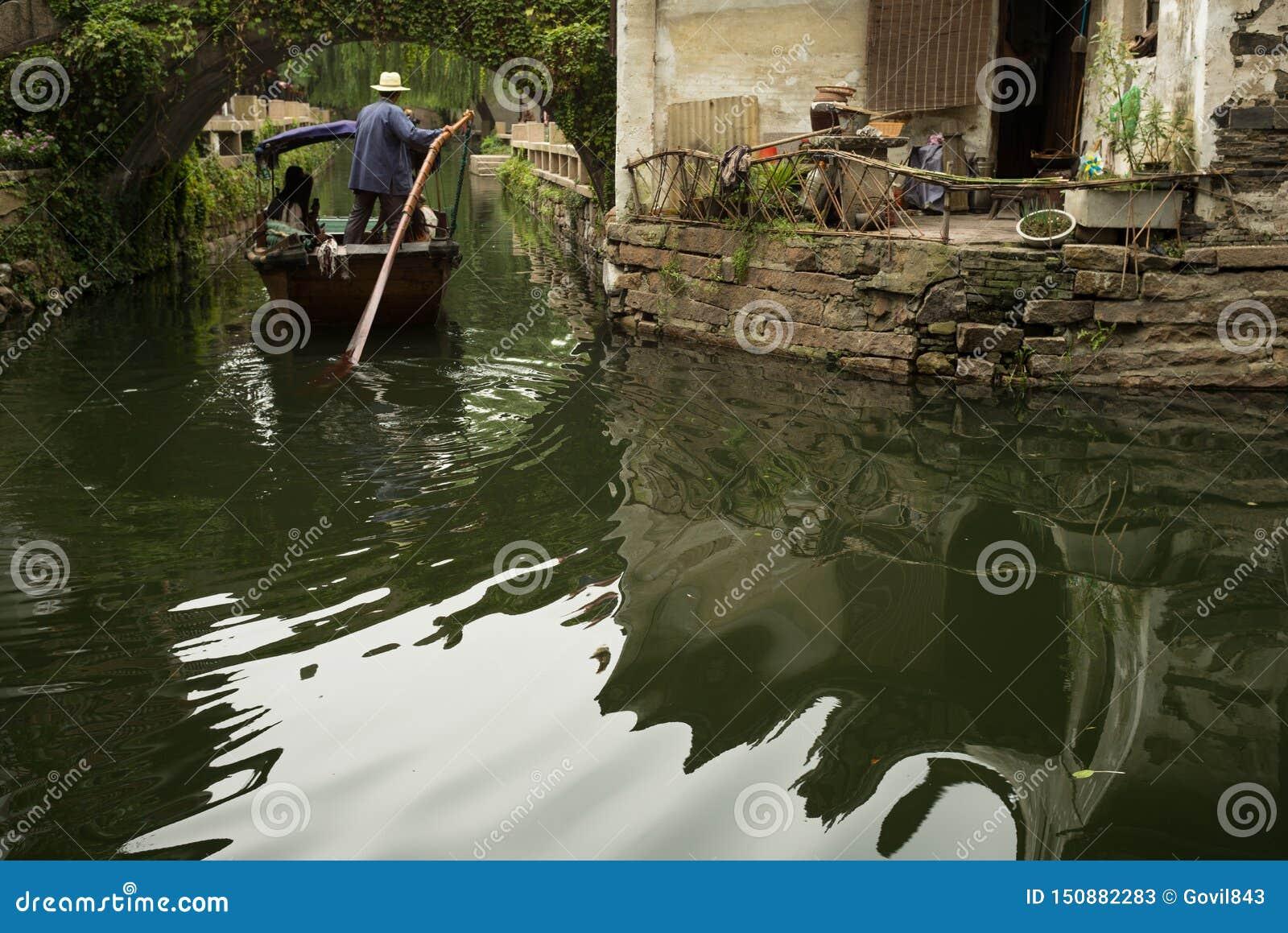 ZHOUZHUANG, CHINA: Boot die door kanalen overgaan