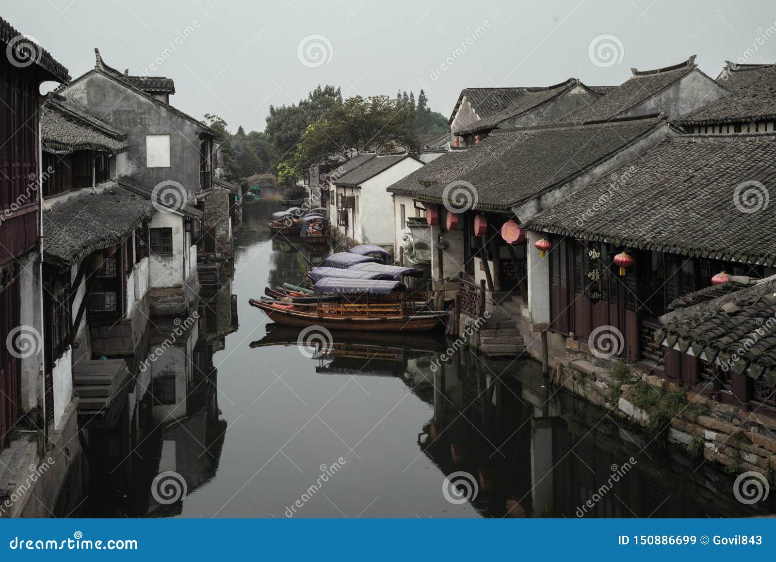 ZHOUZHUANG, CHINA: Casas viejas y reflexión del barco en un canal del pueblo