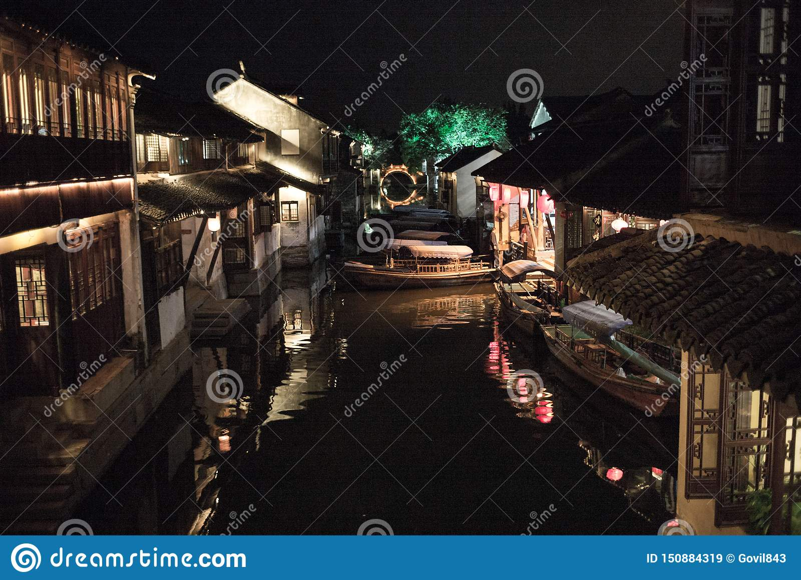 ZHOUZHUANG, CINA: Vecchie case e riflessione del ponte in un canale del villaggio