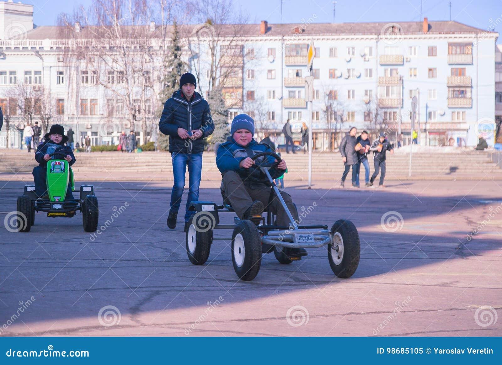 Zhytomyr, Ucrania - 5 de mayo de 2015: Dos muchachos de los niños en ropa colorida y la conducción de los coches del juguete