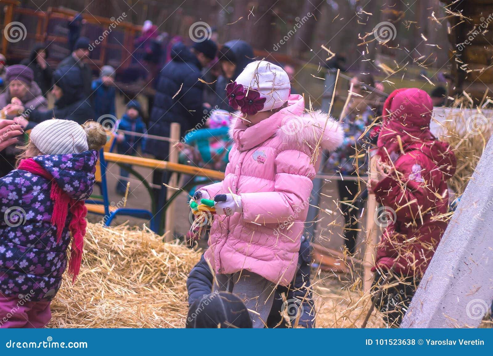 Zhytomyr, Ukraine - 19. November 2016: Lustige kleine glückliche Mädchen, die Spaß mit Heu auf einem Bauernhof haben