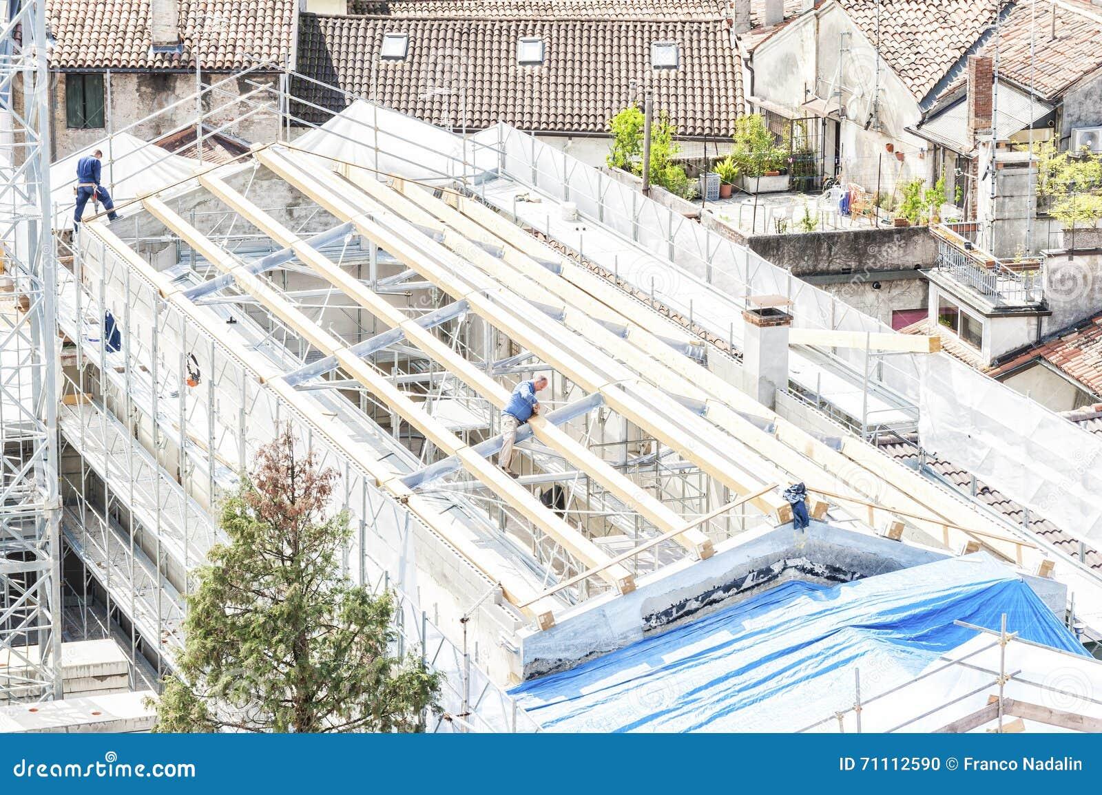 Ziegelsteine, die draußen legen Baumannschaft, die an dem Dach sheetin arbeitet
