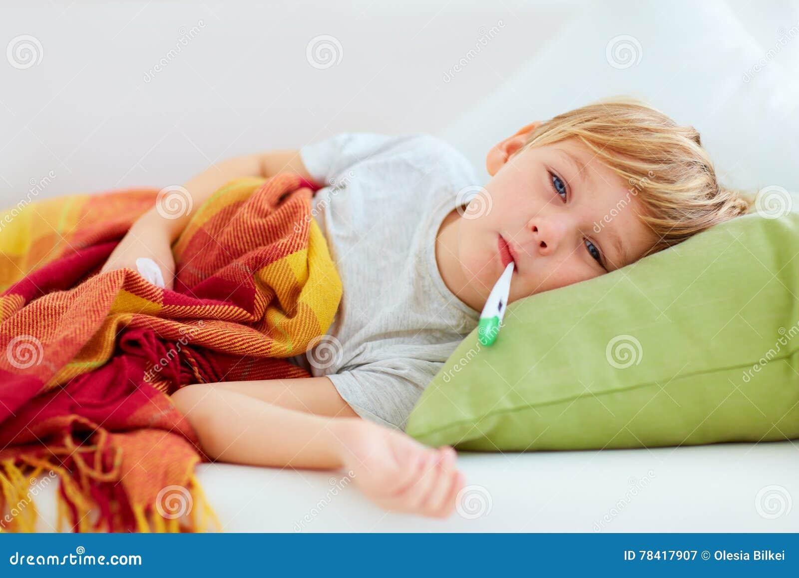 Ziek jong geitje met lopende neus en koortshitte die op laag thuis liggen