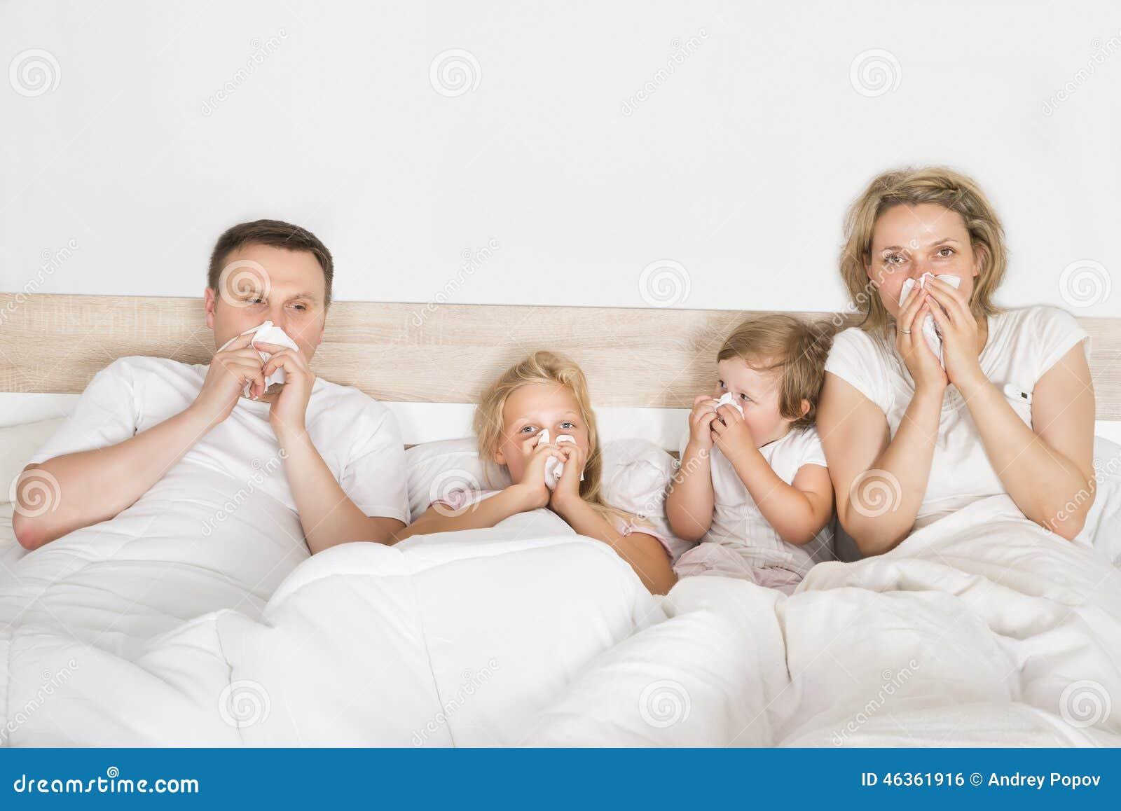 Zieke familie die in bed liggen