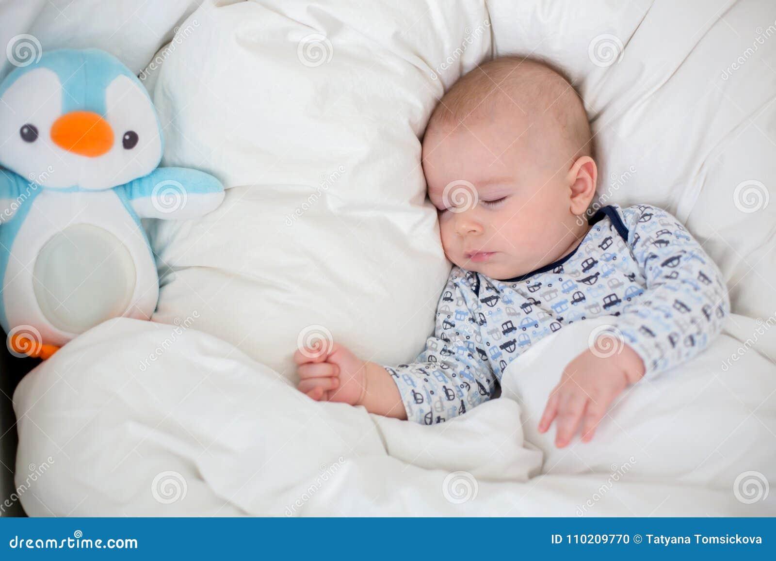 Zieke kindjongen die in bed met een koorts liggen, die thuis rusten