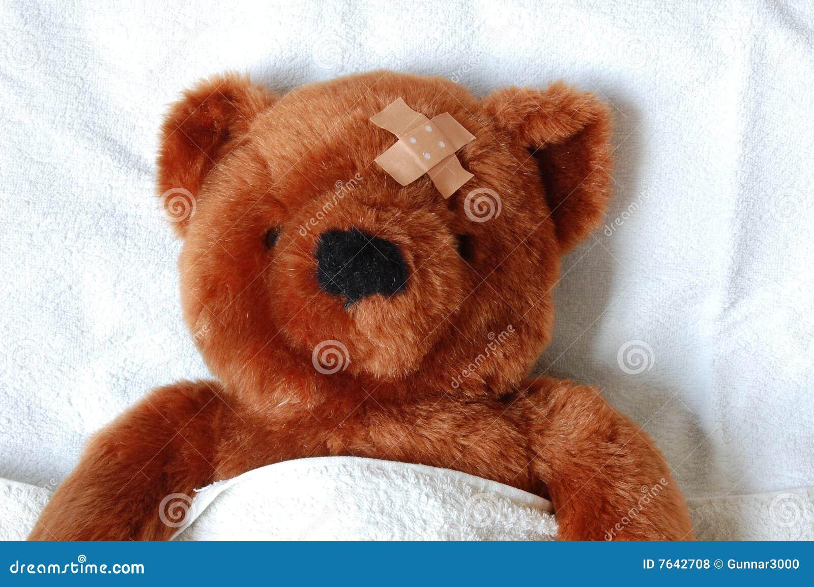 Zieke teddy met verwonding in bed