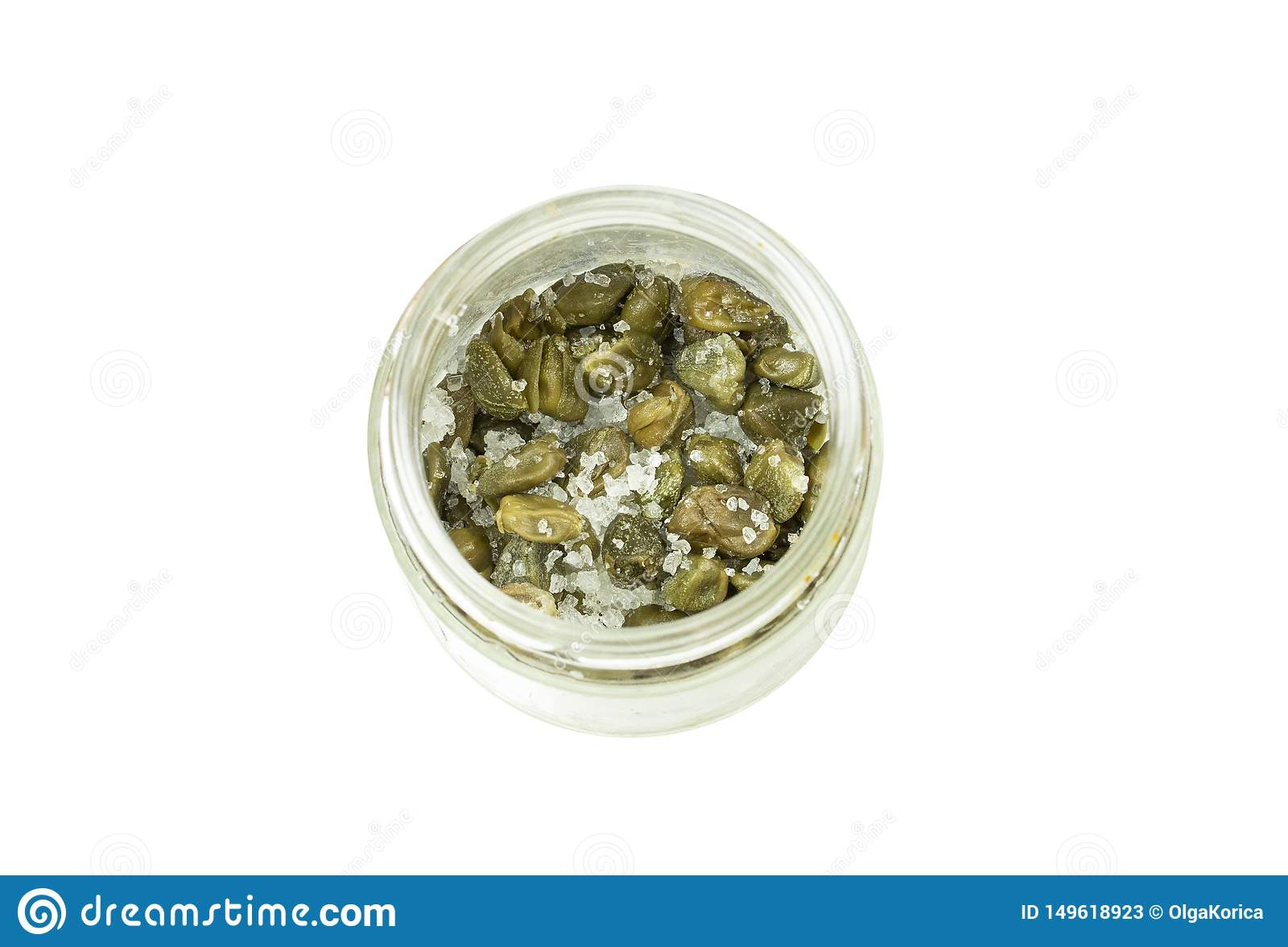Zieleń kapary z prostacką solą w szklanym słoju odizolowywającym na białym tle, odgórny widok Słonej warzywo pikantności kulinarn