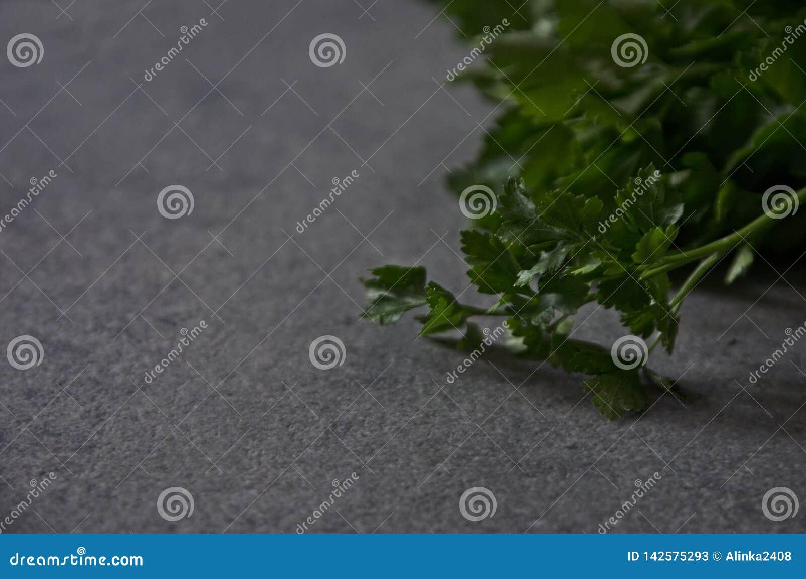 Zielenieje pietruszki na stole w górę, tło