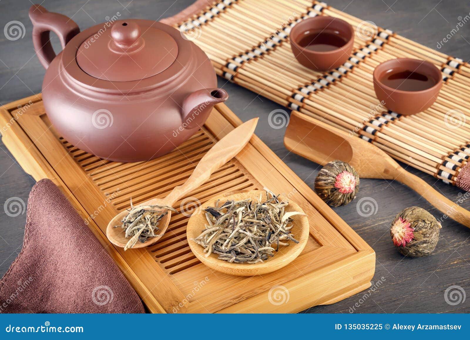 Zielona herbata i atrybuty dla herbacianej ceremonii - ceramiczny teapot, filiżanki, durszlak, chopsticks i pincety, umieszczamy