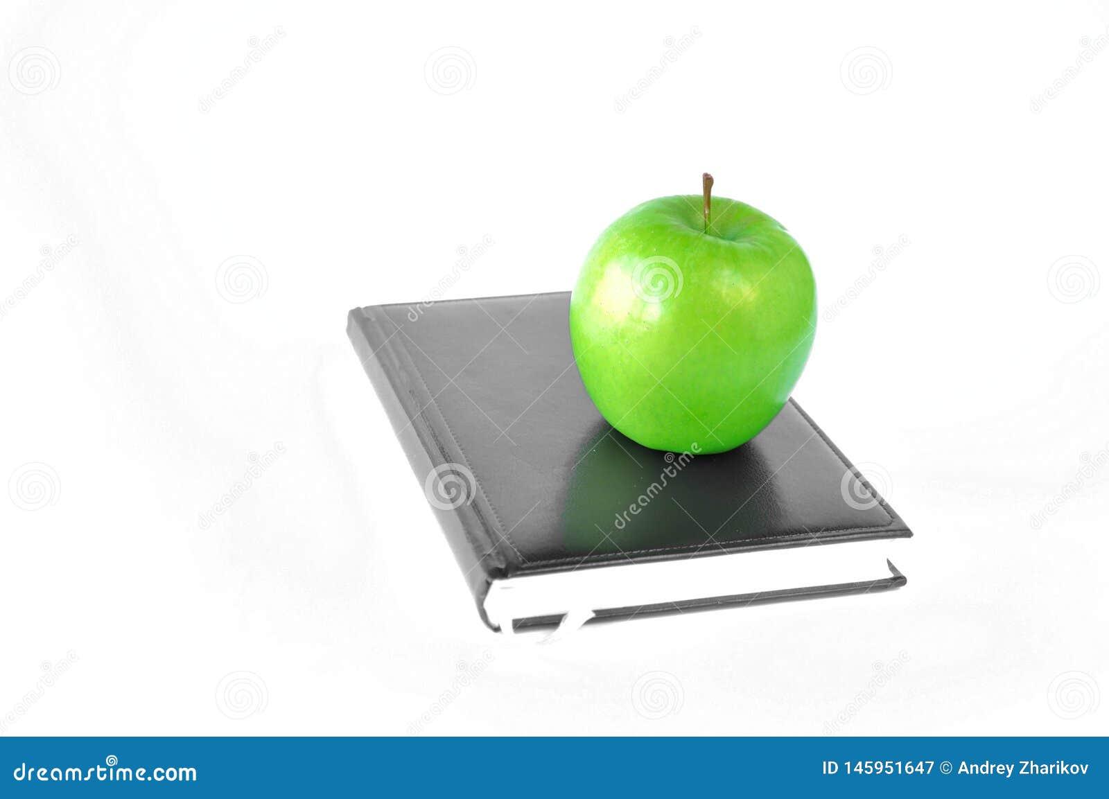Zielona jabłczana pozycja na książce na białym tle lub notatniku