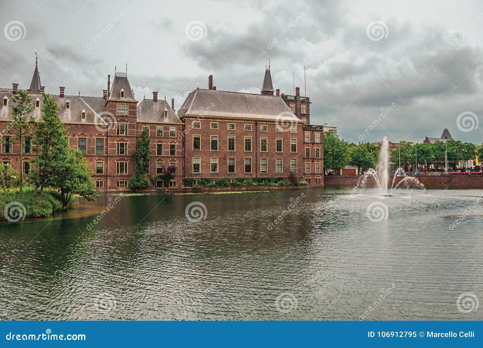 Zielona wyspa na Hofvijver jeziorze z Binnenhof Gockimi rządowymi budynkami chmurnym niebem w Haga i