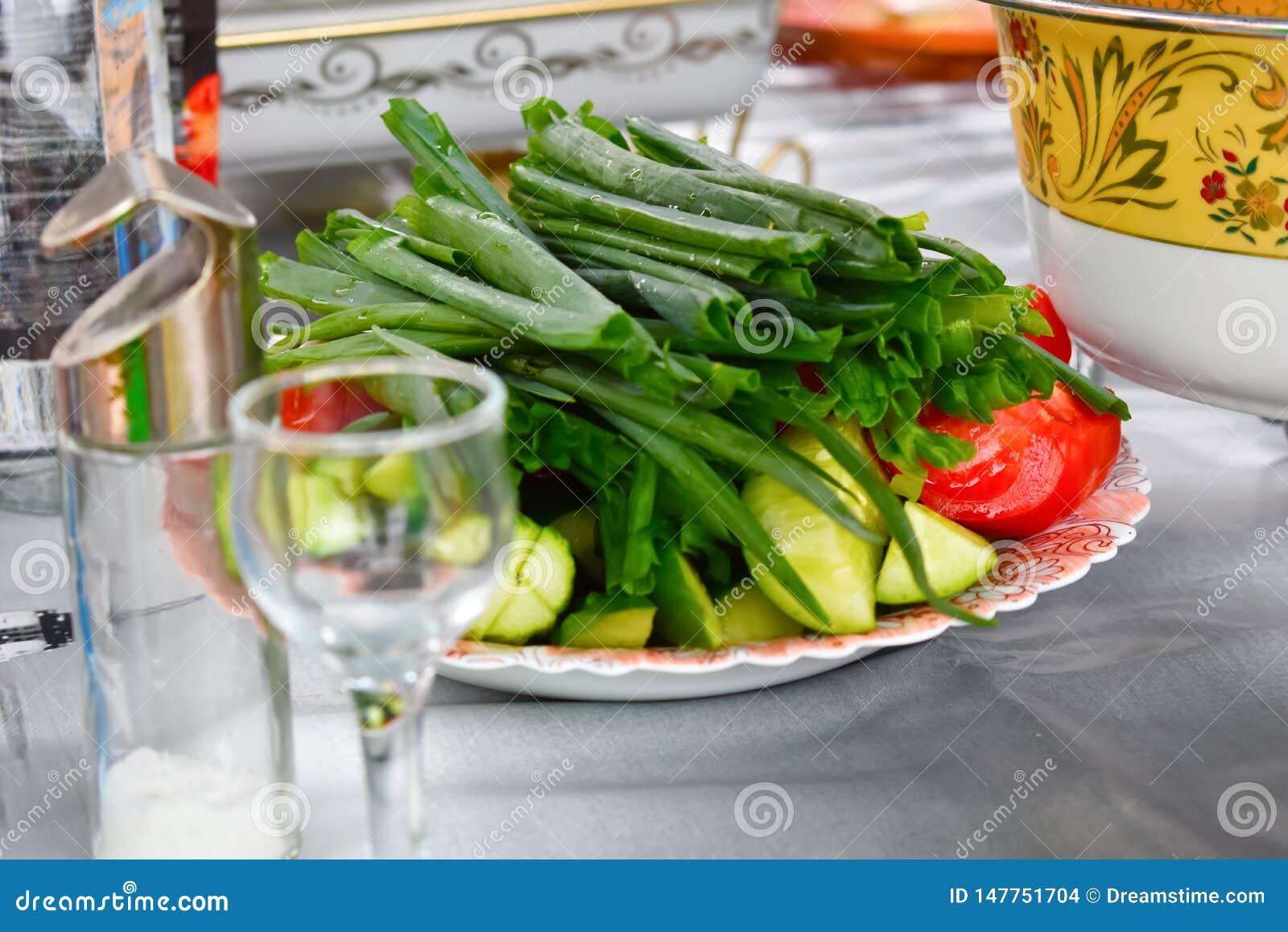Zielone cebule, ogórki i pomidory na naczyniu, zamykają w górę