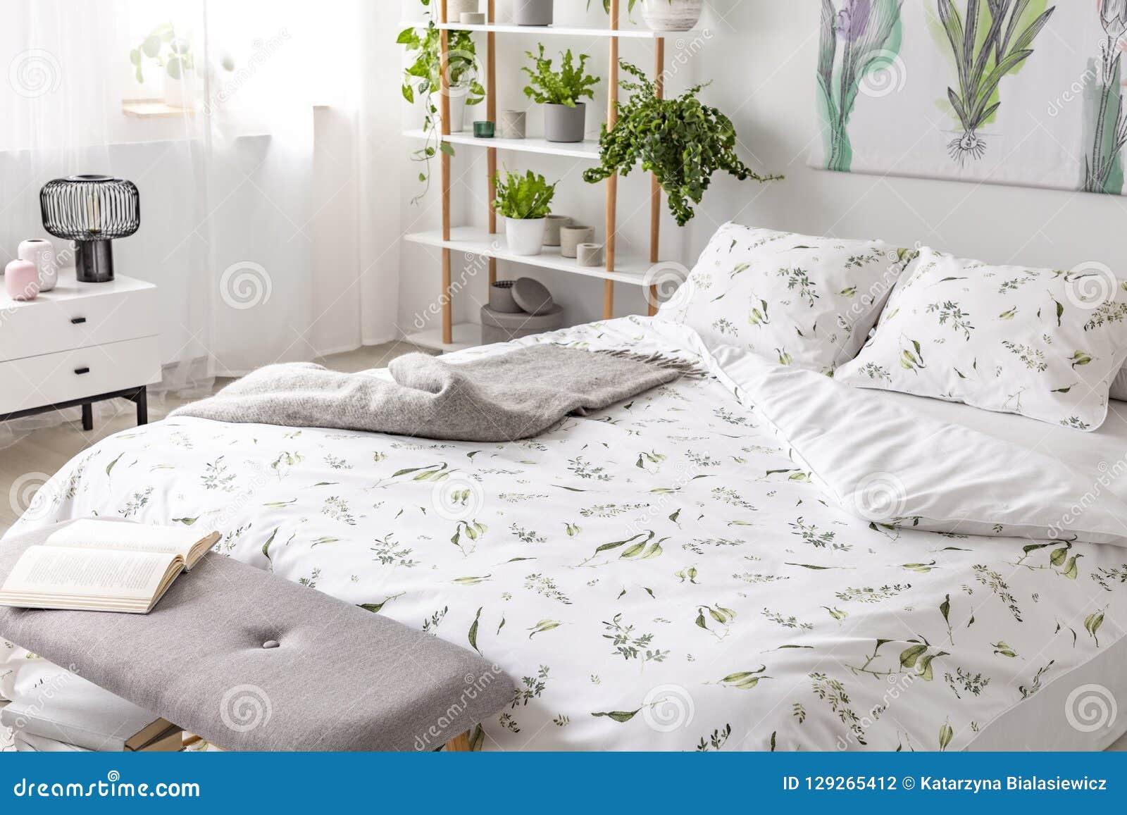 Zielonej rośliny wzór na białej pościeli i poduszki na łóżku w natury sypialni kochającym wnętrzu
