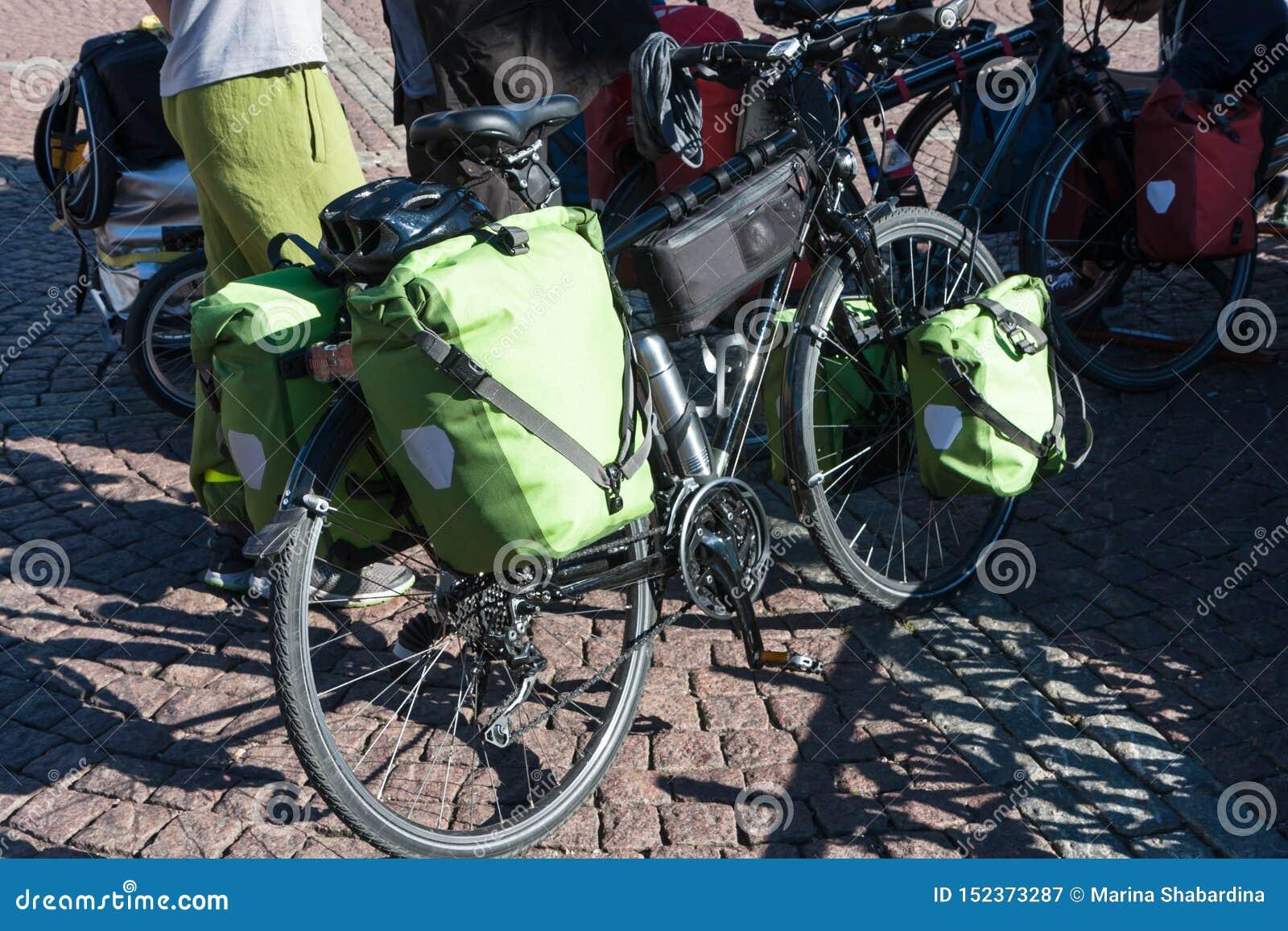 Zielony bicykl zdojest dla długich podróży na tle brukowi kamienie