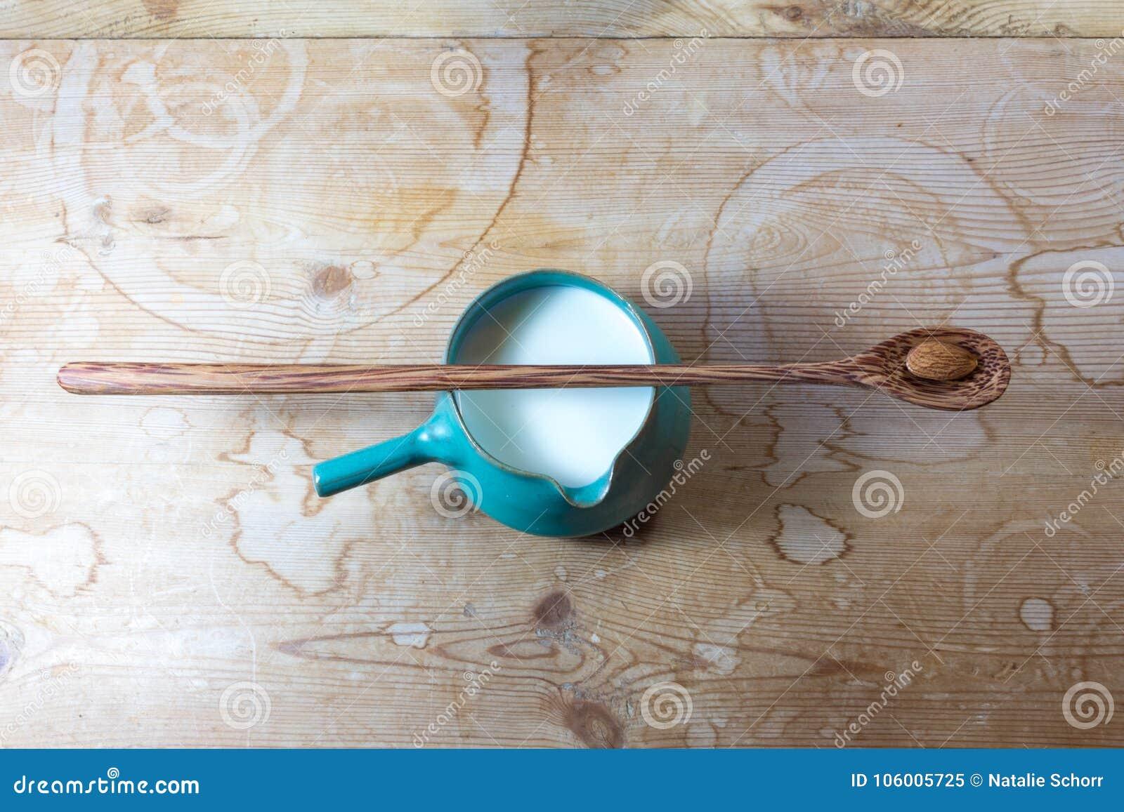 Zielony boczny rękojeść pucharu miotacz migdału mleko, centrowany, bardzo tęsk drewniana łyżka z pojedynczym migdałem balansujący