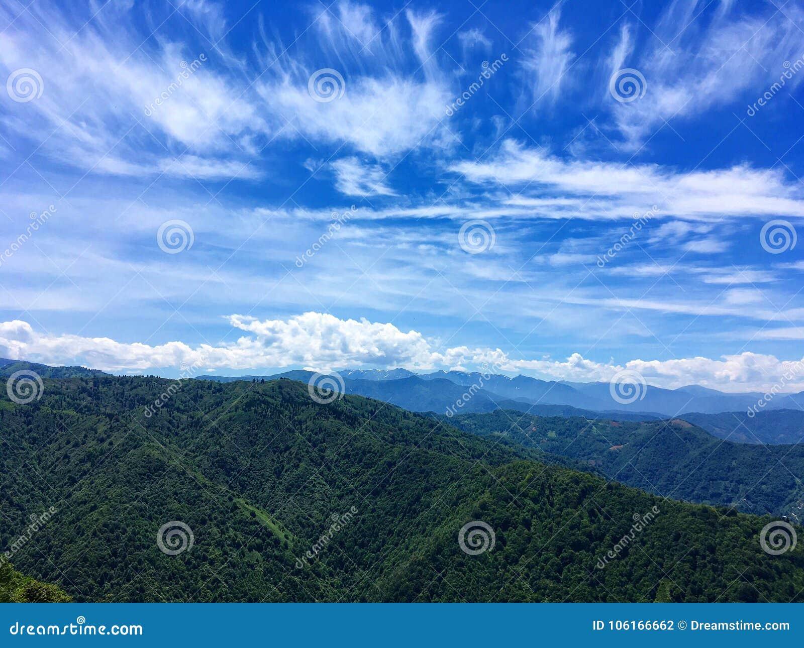 Zielony halny łańcuch pod niebieskim niebem