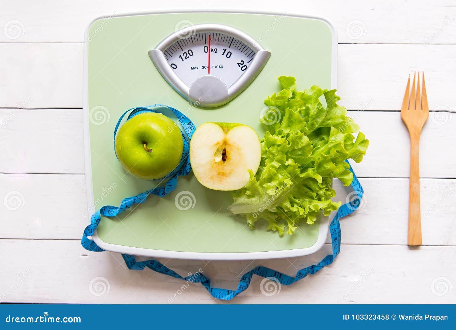 Zielony jabłko, świeży warzywo z ciężar skala i pomiarowa taśma dla zdrowej diety odchudzania,
