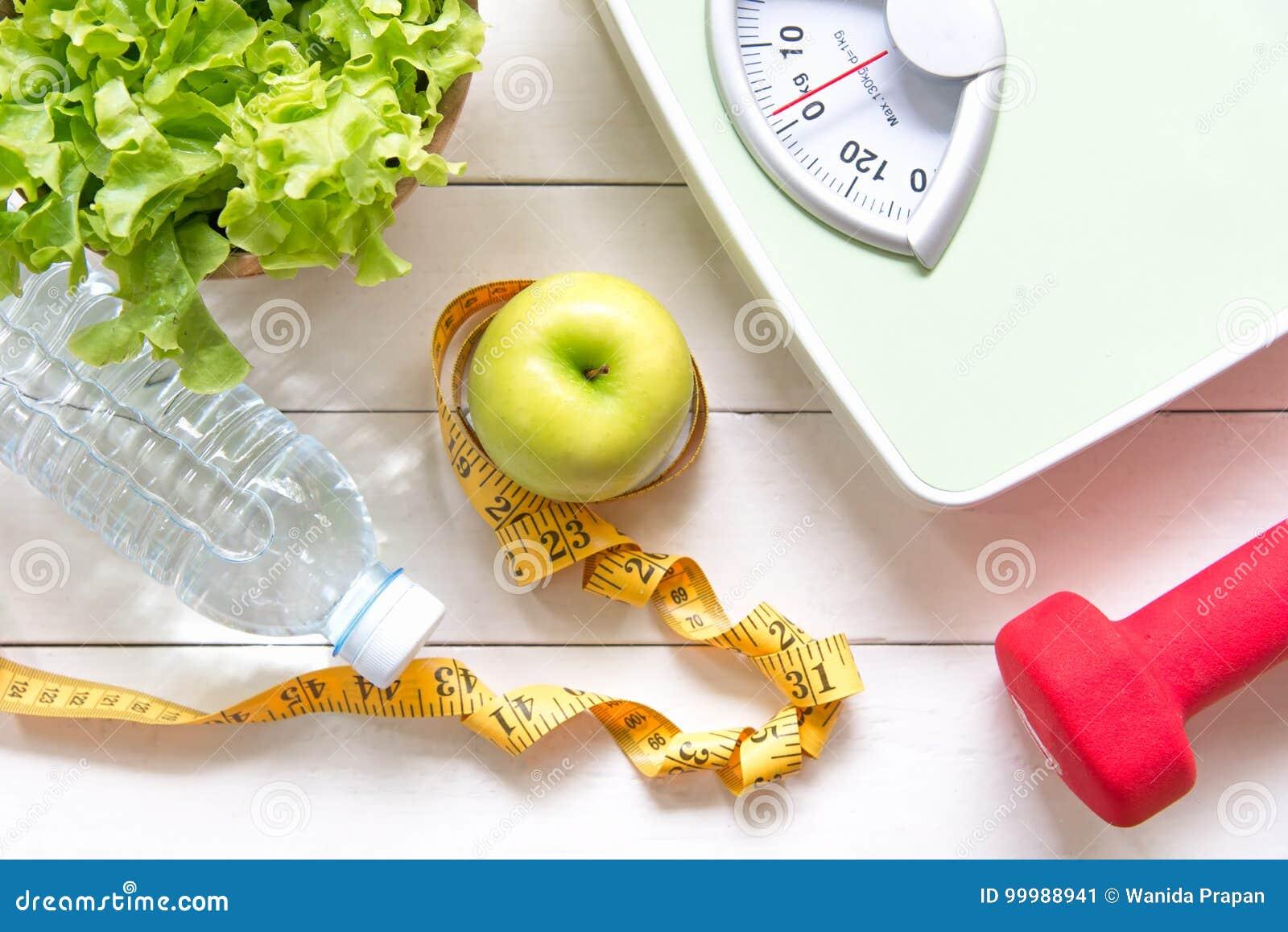 Zielony jabłko i ciężar ważymy, miara klepnięcia z świeżym warzywem, czysta woda i sporta wyposażenie dla kobiety diety odchudzan