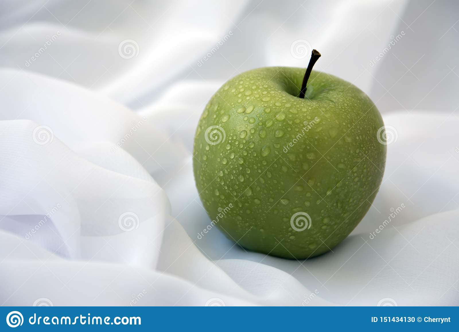 Zielony jabłko na białym tle z wodnymi kropelkami,
