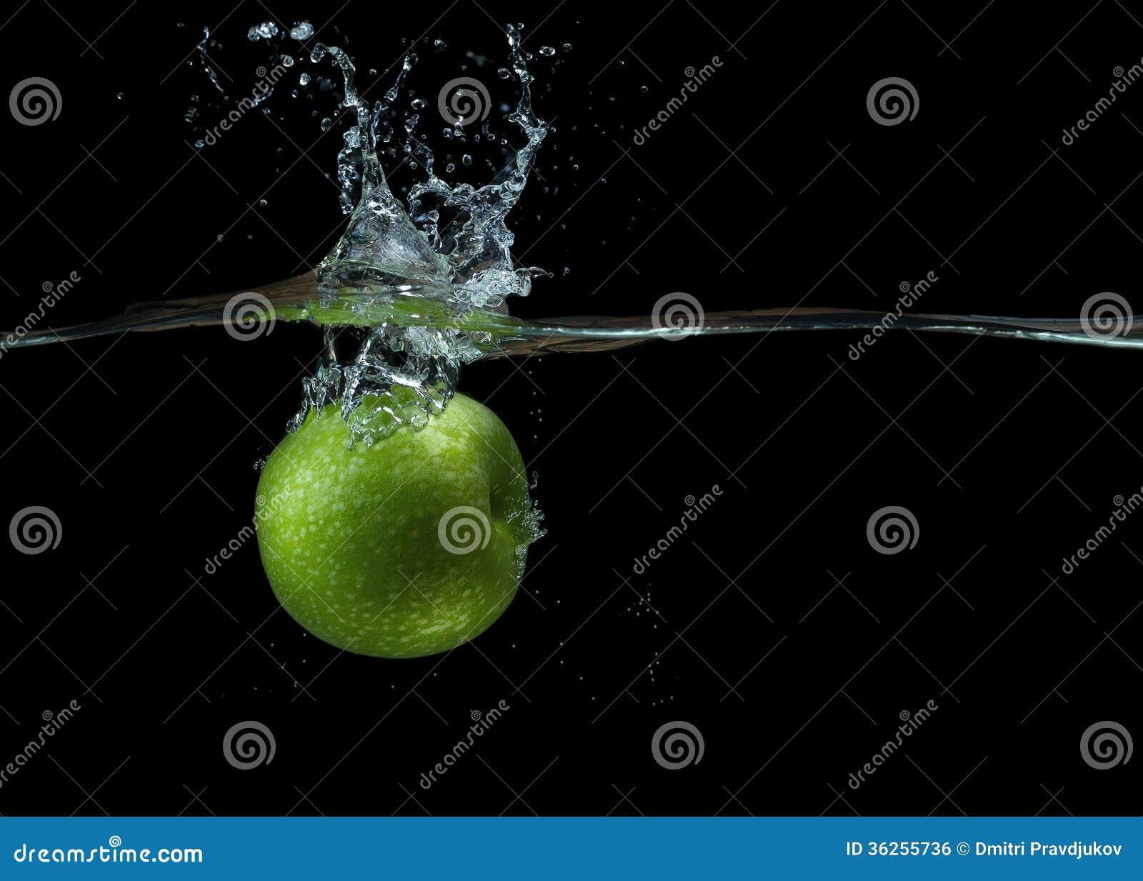 Zielony jabłko w wodzie z pluśnięciem