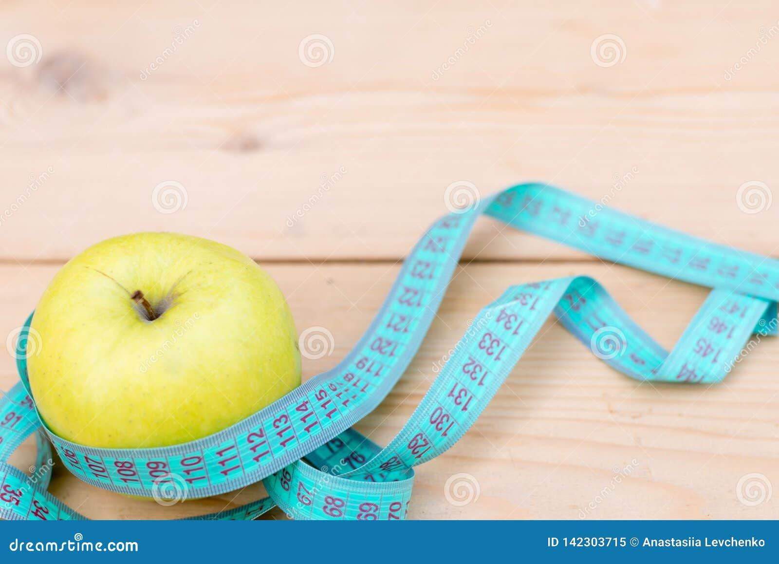 Zielony jabłko z pomiarową taśmą na drewnianym tle pojęcie diety kosmos kopii