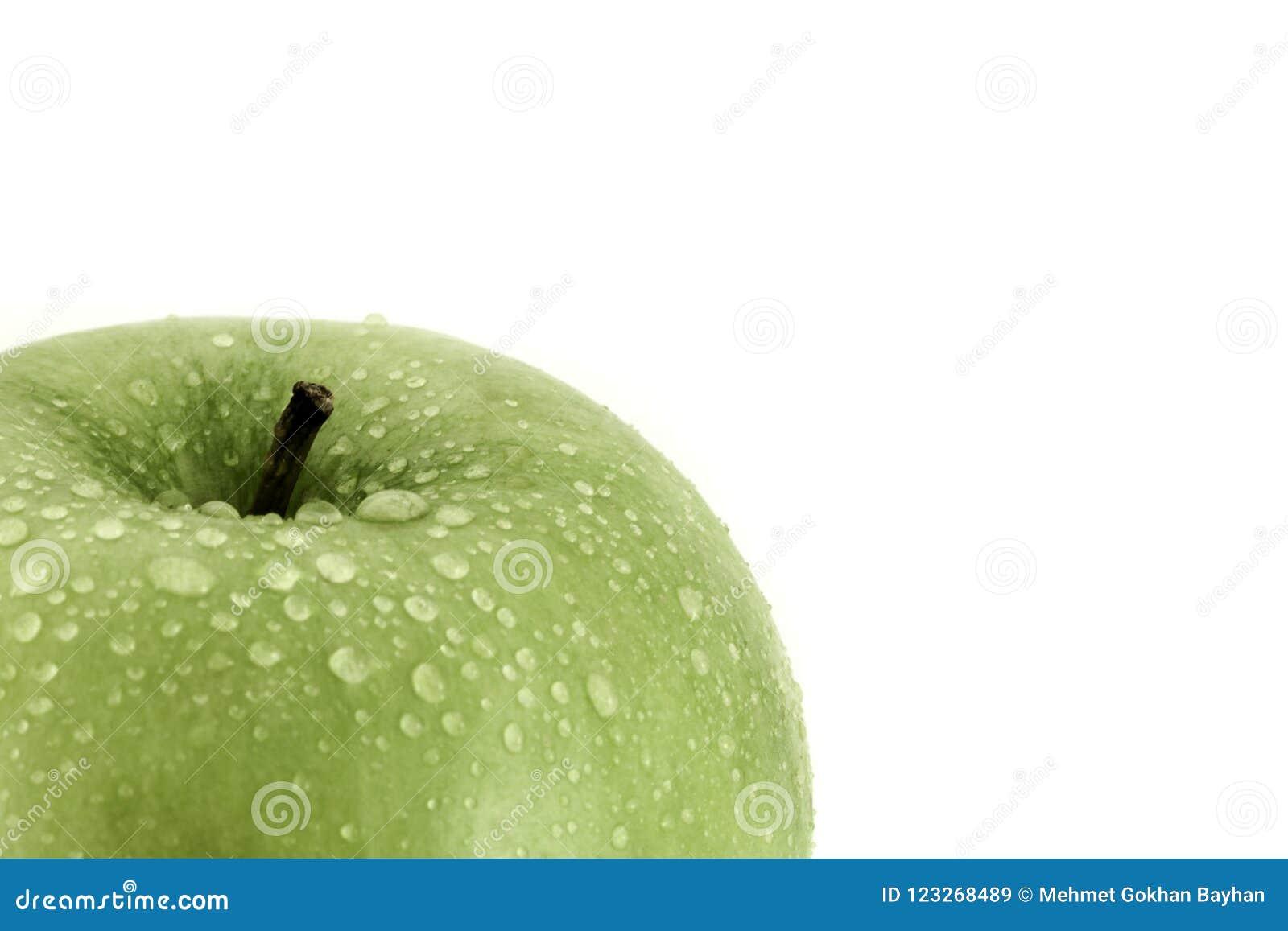 Zielony jabłko z wodnych kropelek zakończenia strzałem na bielu z kopii przestrzenią dla teksta