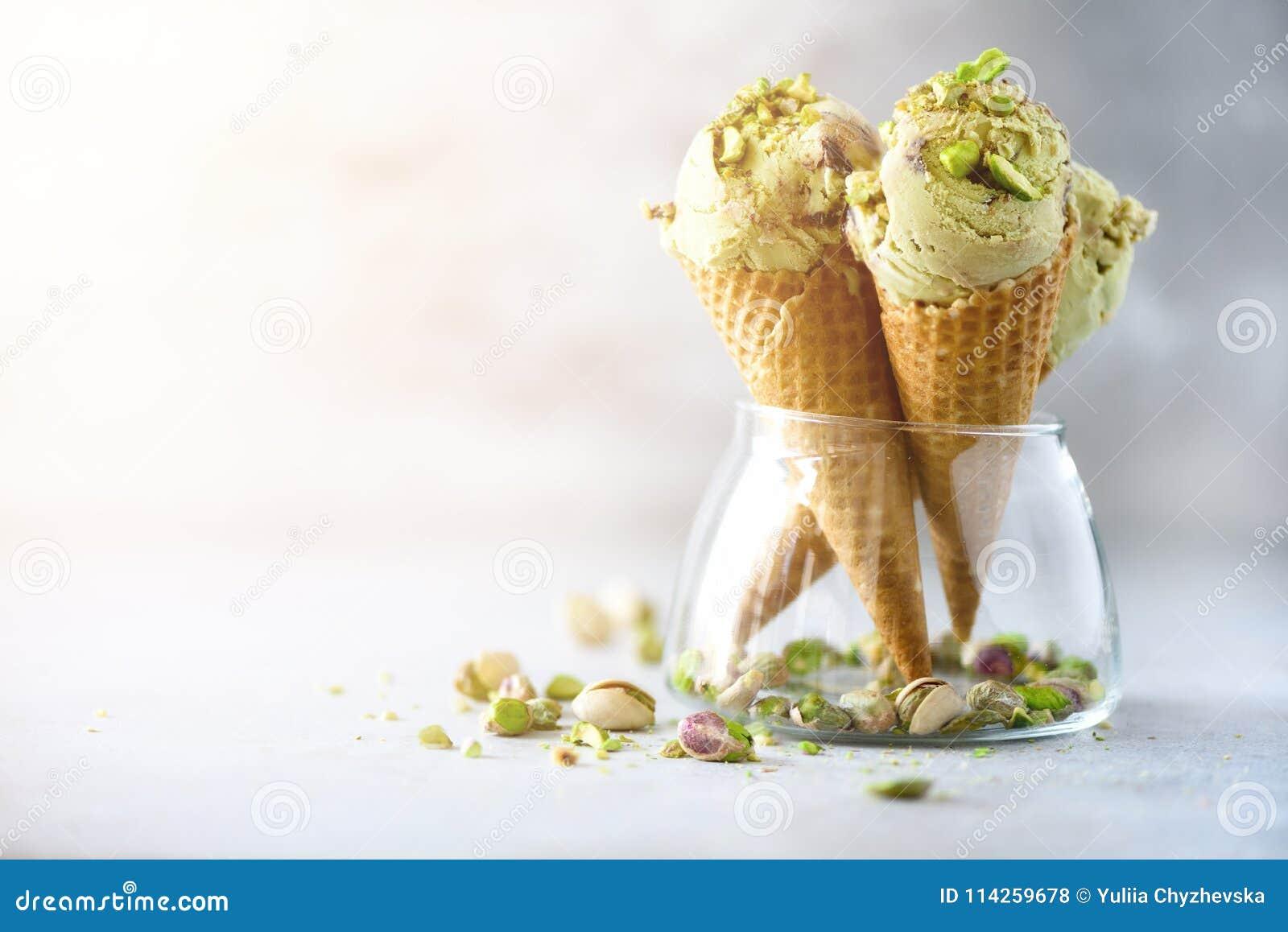 Zielony lody w gofra rożku z czekoladowymi i pistacjowymi dokrętkami na popielatym kamiennym tle Lata karmowy pojęcie, kopia