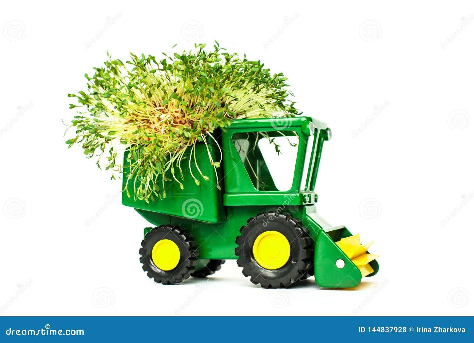 Zielony zabawkarski rolniczy ciągnik, zbierający, uprawiający ziemię maszynerię na białym tła miejscu dla teksta, odizolow