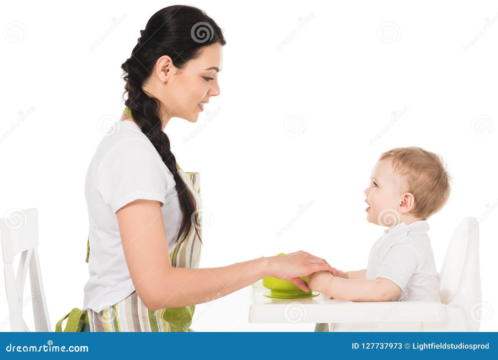 Zijaanzicht van de handen van de moederholding van babyjongen in highchair