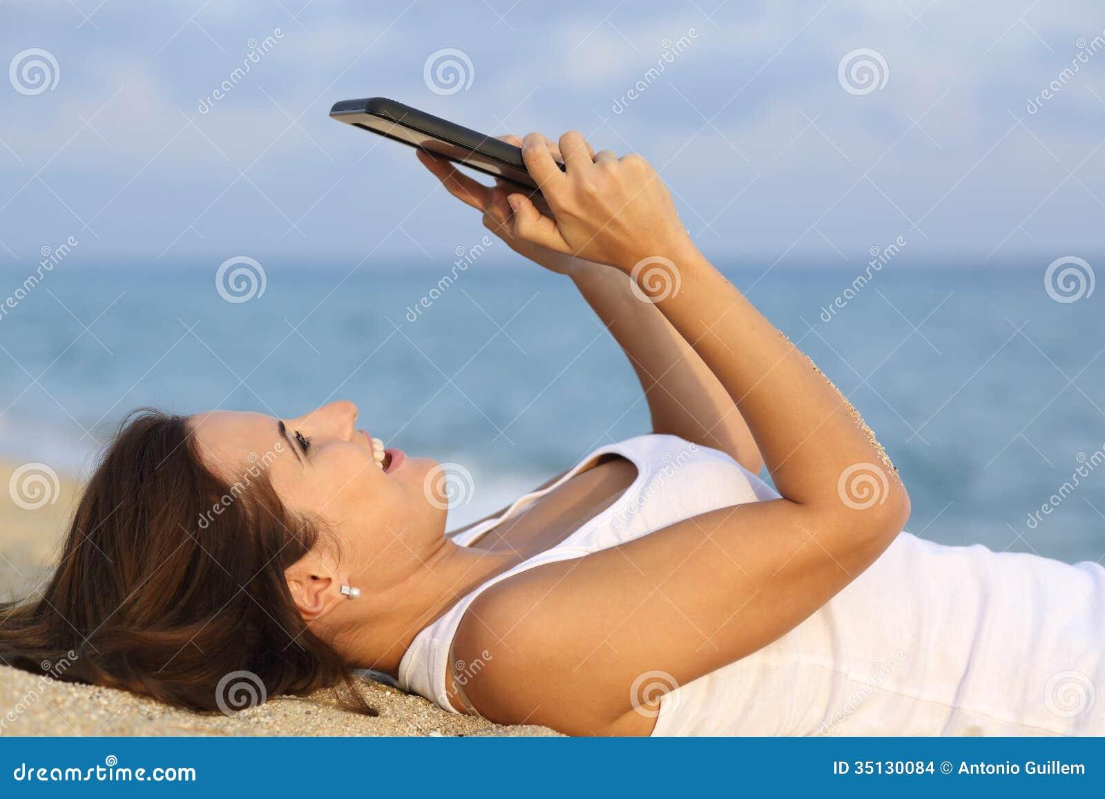Zijaanzicht van een tienermeisje die haar tabletpc doorbladeren die op het zand van het strand liggen