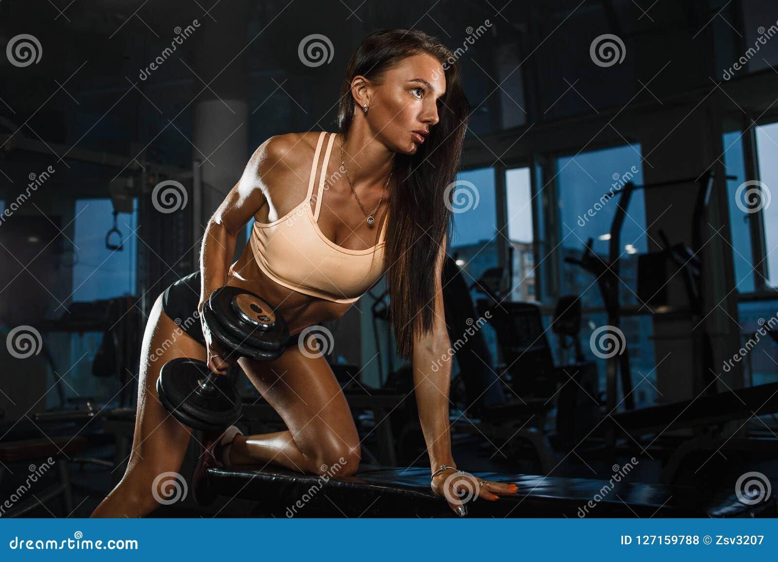Zijaanzicht van jong sportief meisje die harde domoren op bank in gymnastiek opheffen
