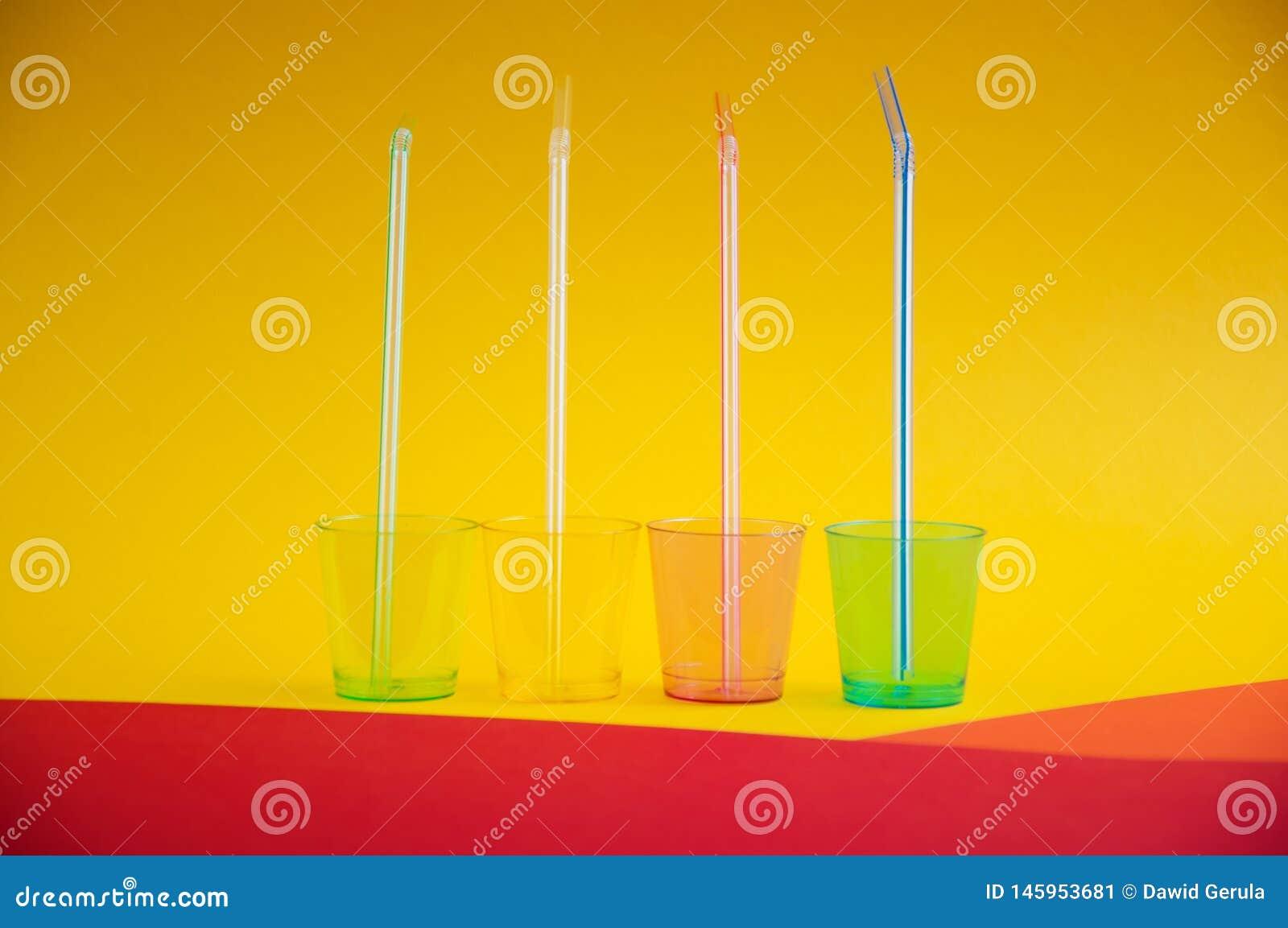 Zijaanzicht van kleurrijke lege plastic glazen met stro binnen hen, op multikleurenachtergrond